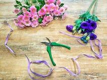 Fond floral - un bouquet des chrysanthèmes et un bouquet de l'eustoma pourpre avec les cisaillements du fleuriste et du raphia su photos stock
