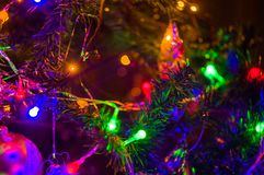 Fond-guirlandes de Noël avec les lumières colorées sur un arbre de Noël décoré, bokeh image stock