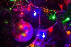 Fond-guirlandes de Noël avec les lumières colorées sur un arbre de Noël décoré, bokeh image libre de droits