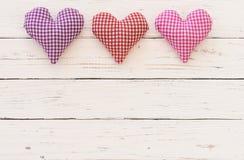 Fond heureux de carte de jour de valentines ou de jour de mères avec trois coeurs d'amour sur le bois blanc Image stock
