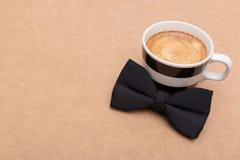 Fond heureux de jour du ` s de père Tasse de café et de noeud papillon noir sur la configuration brune d'appartement de fond Jour Photo stock