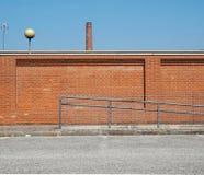 Fond industriel urbain Un mur de briques avec une vieille cheminée d'usine devant une route bétonnée Photographie stock libre de droits