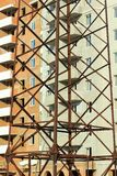 Fond industriel vertical de résumé du bâtiment à plusiers étages de brique en construction derrière la tour haute étroite de pylô photographie stock libre de droits