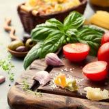 Fond italien de nourriture avec des tomates de vigne, basilic, spaghetti, ingrédients d'olives sur la table en pierre Images stock