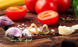 Fond italien de nourriture avec des tomates de vigne, basilic, spaghetti, ingrédients d'olives sur la table en pierre Photo stock