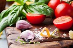 Fond italien de nourriture avec des tomates de vigne, basilic, spaghetti, ingrédients d'olives sur la table en pierre Photo libre de droits