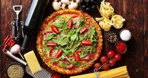 Fond italien de nourriture avec la pizza, les pâtes crues et les légumes sur la table en bois banque de vidéos