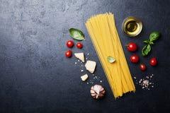 Fond italien de nourriture avec les spaghetti, la tomate, les feuilles de basilic, le fromage, l'ail et l'huile d'olive crus pour Image stock