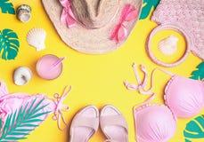 Fond jaune d'été avec le bikini rose, chapeau de paille, lunettes de soleil, sandales avec le cocktail, coquillages, palmettes tr photo stock