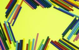 Fond jaune de beaucoup de configurations en bois colorées de bâtons photo stock