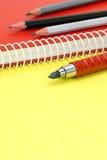 Fond jaune de conseil avec le carnet et les crayons rouges pour le bureau Images libres de droits