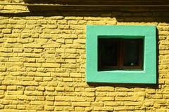 Fond jaune de mur de briques avec la fenêtre verte photographie stock