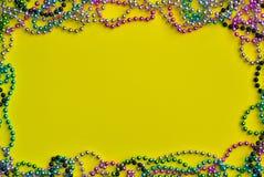 Fond jaune encadré avec des perles de Mardi Gras photos stock