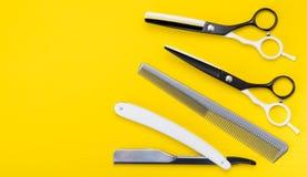 Fond jaune lumineux un ensemble d'articles pour couper des cheveux, des ciseaux, et des peignes, et dangereux photographie stock