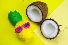 fond jaune vibrant d'été avec le jouet drôle d'ananas en lunettes de soleil et noix de coco image libre de droits