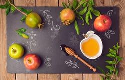 Fond juif de Rosh Hashana de vacances avec les pommes, la grenade et le miel sur le tableau noir Vue de ci-avant Image libre de droits