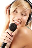 Fond of karaoke. Portrait of a blond in headphones singing karaoke Royalty Free Stock Images