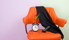 Fond la chaise orange il est, manteau à protéger contre les cheveux, réveil, cheveux d'Electromashina photo stock