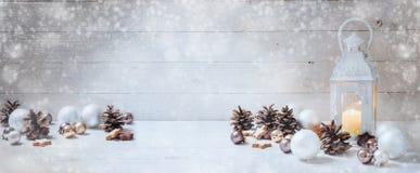 Fond large de Noël avec une lanterne de lumière de bougie, babioles, Image stock