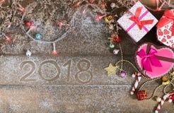Fond, lumière et boîte-cadeau de Noël avec des bottes d'enfant Image stock