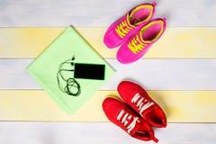 Fond lumineux pour pulser, avec deux paires des chaussures et d'un téléphone de musique photos stock