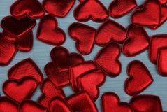 Fond lumineux rouge de petits coeurs sur un fond bleu Photographie stock libre de droits