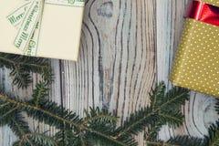Fond minable en bois clair avec un cadre des branches et des cadeaux impeccables Image stock