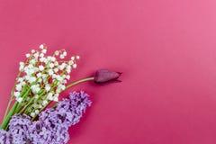 Fond minimalistic de ressort avec les fleurs, les tulipes et les lis lilas de la vallée sur la table blanche photo libre de droits