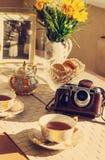 Fond modifié la tonalité avec la tasse du thé, des fleurs d'été, du foto et de l'appareil-photo de vintage Image stock
