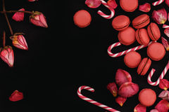 Fond noir avec des pétales des roses rouges, des macarons et des bâtons de caramel Image libre de droits