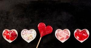 Fond noir avec la rangée des sucreries en bas Photos stock