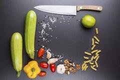 Fond noir avec les ingrédients végétaux pour la cuisson Courgette, poivrons, tomates, ail, chaux, écrous et sel de mer Photographie stock libre de droits