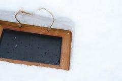 Fond noir de conseil avec la neige l'hiver Photographie stock libre de droits