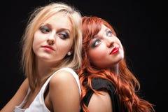 Fond noir de deux jeunes amies heureuses Photographie stock