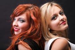 Fond noir de deux jeunes amies heureuses Image stock