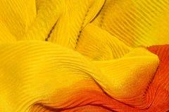 Fond ondulé jaune-orange de tissu Image stock