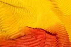 Fond ondulé jaune-orange de tissu Photographie stock