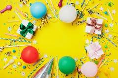 Fond ou cadre de fête d'anniversaire avec le ballon coloré, le cadeau, les confettis, l'étoile argentée, le chapeau de carnaval,  image libre de droits