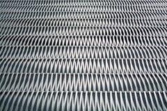 Fond ou texture sur un mur gris un trellis de m?tal un fil qui s'entrelace parmi eux-m?mes Crochets et boucles La g?om?trie de l images libres de droits