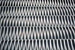 Fond ou texture sur un mur gris un trellis de m?tal un fil qui s'entrelace parmi eux-m?mes Crochets et boucles La g?om?trie de l photographie stock
