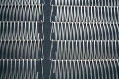 Fond ou texture sur un mur gris un trellis de m?tal un fil qui s'entrelace parmi eux-m?mes Crochets et boucles La g?om?trie de l images stock