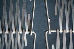 Fond ou texture sur un mur gris un trellis de m?tal un fil qui s'entrelace parmi eux-m?mes Crochets et boucles La g?om?trie de l image stock