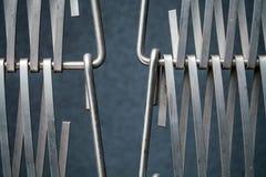 Fond ou texture sur un mur gris un trellis de m?tal un fil qui s'entrelace parmi eux-m?mes Crochets et boucles La g?om?trie de l photos stock