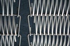 Fond ou texture sur un mur gris un trellis de m?tal un fil qui s'entrelace parmi eux-m?mes Crochets et boucles La g?om?trie de l photographie stock libre de droits