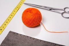 Fond pour le fil orange de tailleur et les outils de couture Image stock