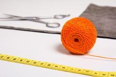 Fond pour le fil orange de tailleur et les outils de couture Photo libre de droits