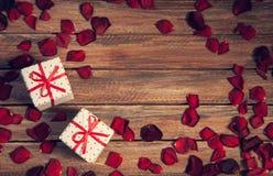 Fond romantique avec des pétales de rose et des présents pour deux Photo stock