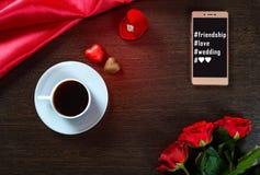 Fond romantique avec l'anneau de mariage, les fleurs roses, le smartphone, la tasse de café et les bonbons au chocolat Image stock