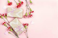 Fond romantique avec les fleurs et le boîte-cadeau d'oeillets sur le rose Photographie stock