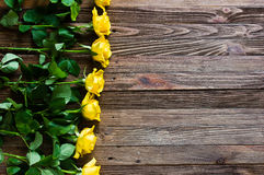 Fond romantique avec les roses jaunes se trouvant sur une table en bois Photo libre de droits